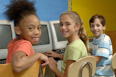 three students posing in front of computers