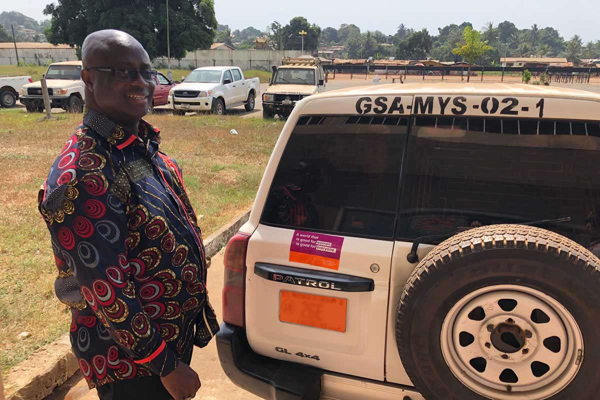 Liberia's Minister of Youth & Sports, Hon. Zeogar Wilson, affixes a WCW bumper sticker to his official vehicle