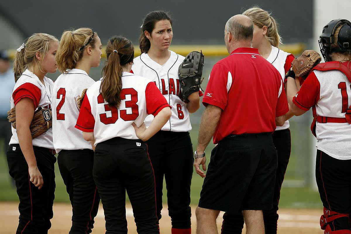 Male coach speaks to girls softball team