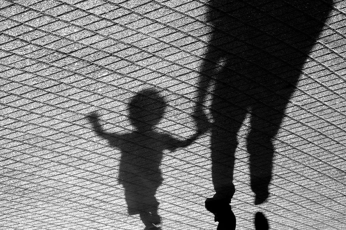 Shadow of adult and child holding hands while walking next to a fence