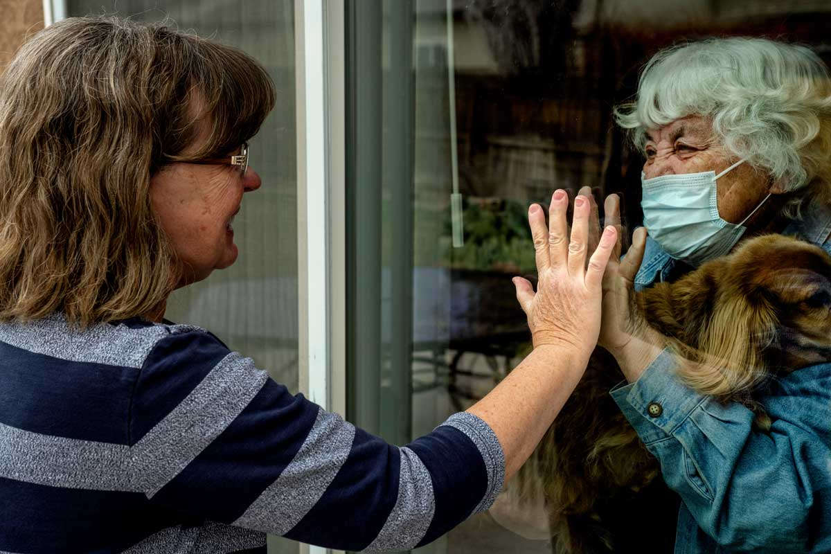Daughter visits mother during quarantine on other side of glass