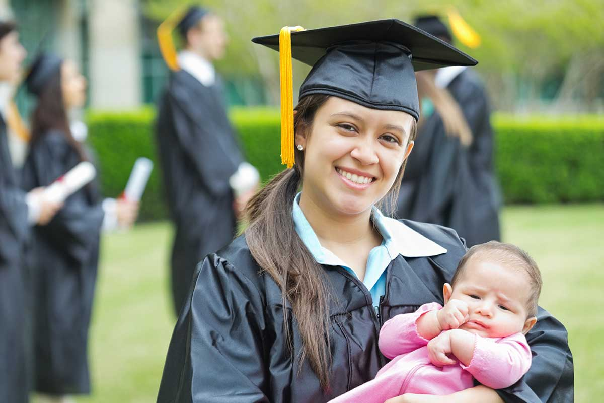 young woman in graduation robes holding child