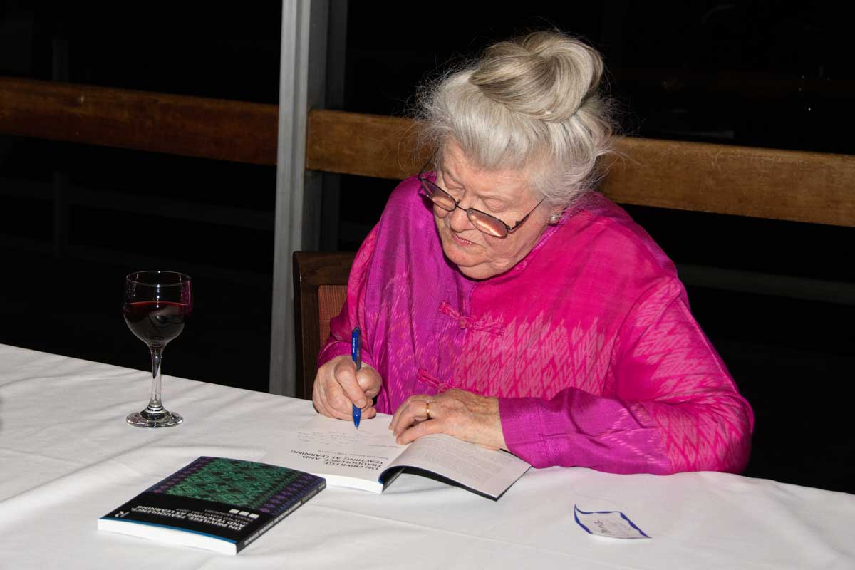 Peggy McIntosh signs a copy of her book, On Privilege, Fraudulence, and Teaching as Learning