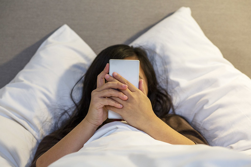 A young girl is looking at a mobile phone in bed.