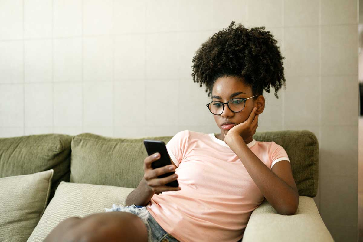 Teenage girl sits on couch and stares at smartphone screen