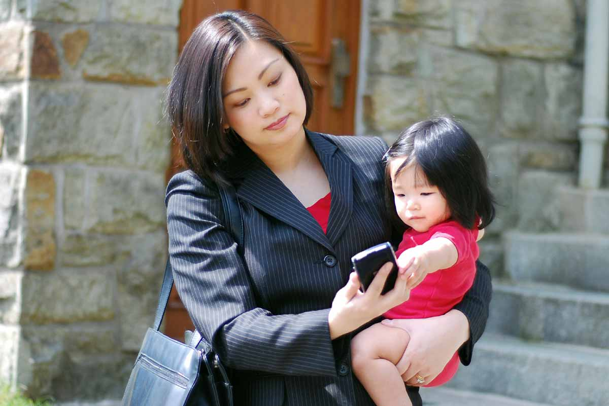 Business woman looks at cellphone while holding baby