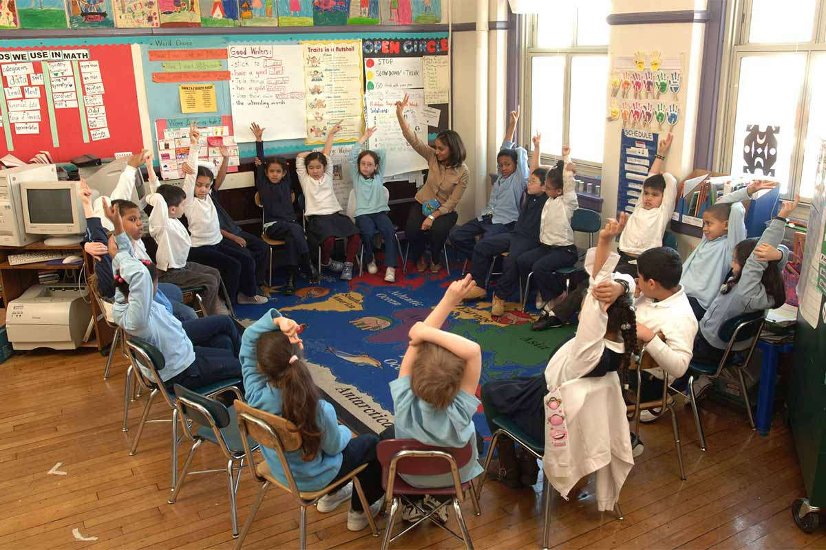 Elementary classroom teacher and students seated in a circle
