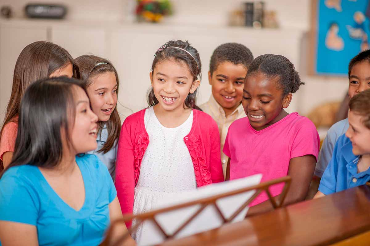 A diverse, happy group of kids stand around a piano singing