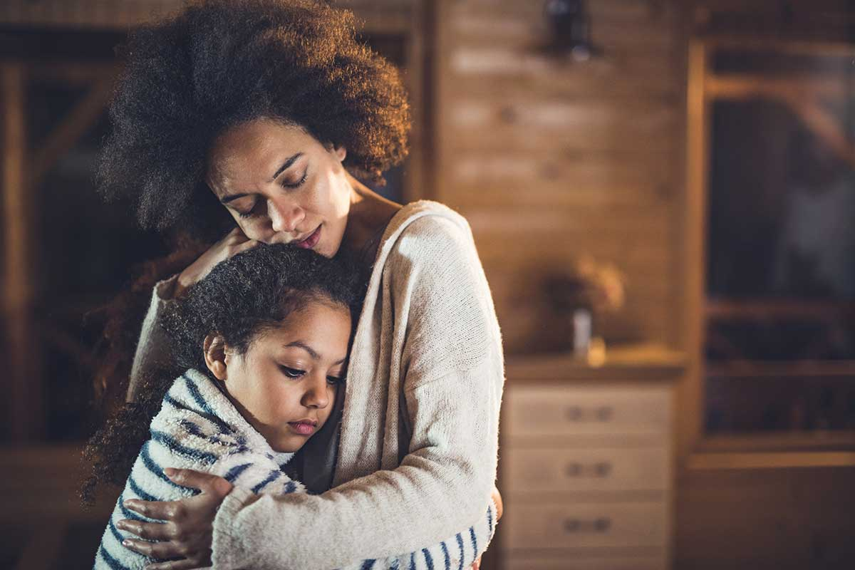 Sad African American mother and child embrace