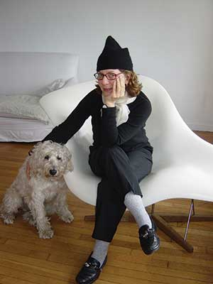 Maira Kalman sitting in a chair with a dog next to her