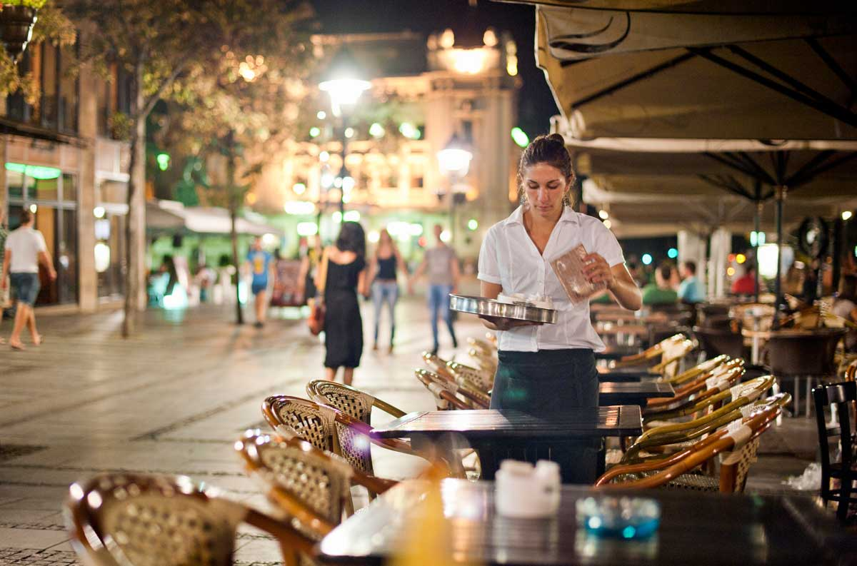 A woman working as a server clears an outdoor cafe table.
